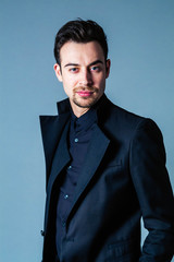 Portrait of a young handsome man in a suit, standing and looking at the camera, against plain studio background.
