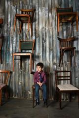 sad boy in checkered shirt sitting