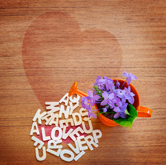 Wood Letters on wood table  with flowers in water can and the word Love; Valentines Day concept