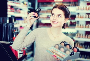 cheerful female customer deciding on make-up items in cosmetics shop