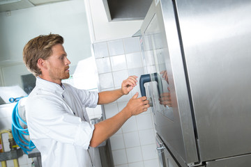 young chef opening restaurant kitchen fridge