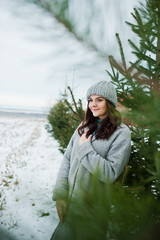 Portrait of gentle girl in gray coat and hat against new year tree outdoor.