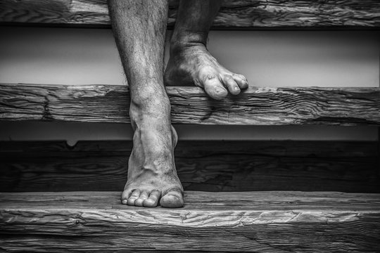Barefoot man stepping down stairs to the basement. Scary dark atmosphere. Phobia concept.