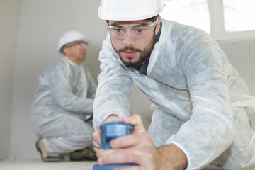 young carpenter sanding with electric sander