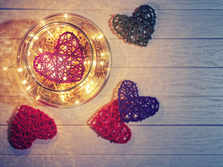 The wicker heart is in a large glass jar with a luminous garland inside and decorative objects. Against the background of light wood there are also several wicker hearts