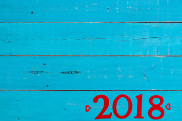 Year 2018 in bold red with hearts border on antique rustic teal blue background; blank holiday sign