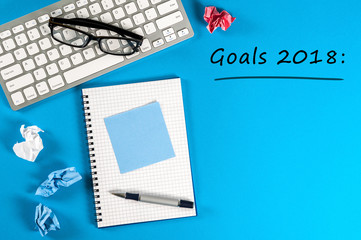 Top view 2018 goals list with keyboard, office supplies on blue desk. Targets, goal, dreams and New Year's promises for the next year