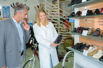 Saleswoman showing medical shoes