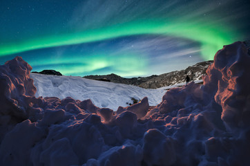 snowdrift in the foreground under an aurora borealis