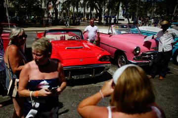 Tourists take photos beside vintage cars in Havana