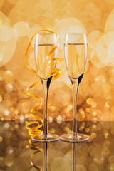 Two glasses of champagne with golden light bokeh on background.