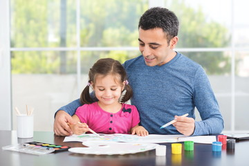 Father Helping Her Preschool Age Daughter Paint Pictures.