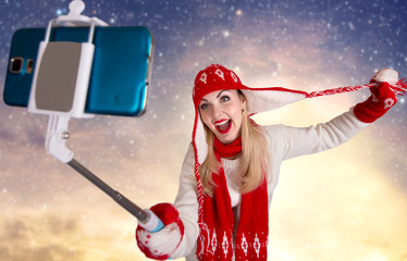 A young woman in a knitted hat scarf and mittens takes pictures of herself on the phone in a winter forest