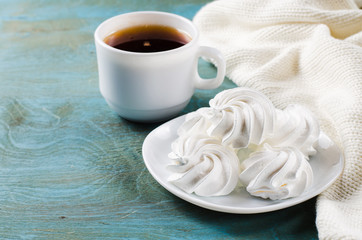 Delicious meringue cookies and cup of hot tea.