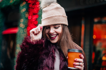Close up outdoor fashion portrait of stylish young woman having fun, emotional face , laughing, looking down. Urban city street style