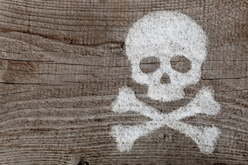 Filled by flour Skull and bones on old wood plank as background