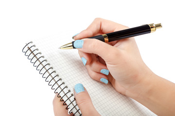 Woman's hand with beautiful manicurewrites pen in notepad.