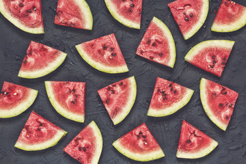 Slices of ripe watermelon on a black stone background