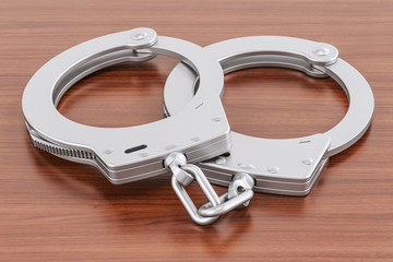 Handcuffs on the wooden table, 3D rendering
