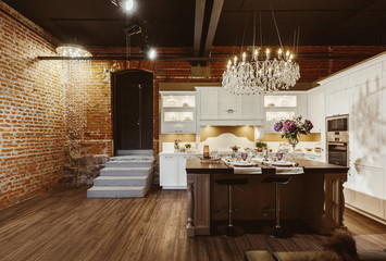 Modern kitchen with luxury candelabra lamp white furniture and brick wall