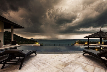 Storm coming up and dark clouds above Swimming pool with sea view in luxury villa, weather and rainy season