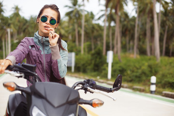 Portrait of female Biker sitting on big motorcycle. Outdoor lifestyle portrait