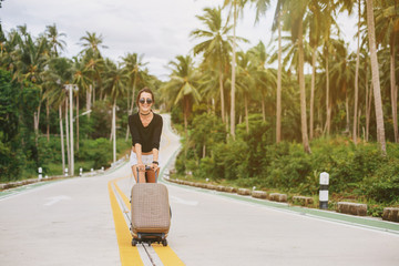 Beautiful style girl walking with suitcase on tropical road