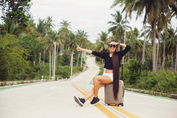 Beautiful style girl sitting on travel suitcase on tropical road. Vacation, travel, hitch-hiking consept