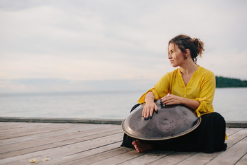 Woman playing on hang drum outdoor on sea shore