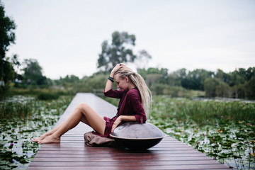 Woman wearing dread locks sitting with hang drum outdoor on beautiful lake