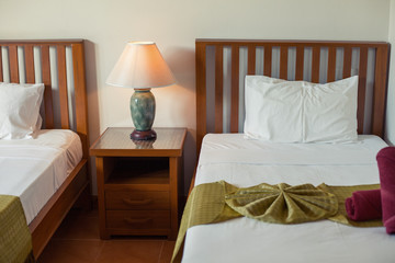 Twin beds and lamp table in asian hotel house bedroom