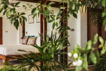 Modern bed room interior in Luxury villa. White colours, glass wall, tropical jungle outside