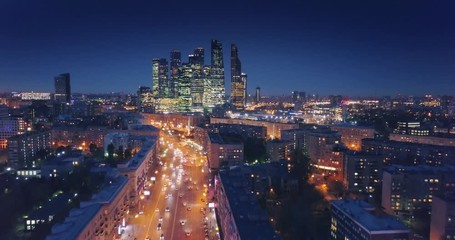 Fotobehang - Aerial view of Moscow City skyline at night. Camera flying backwards. Russia.