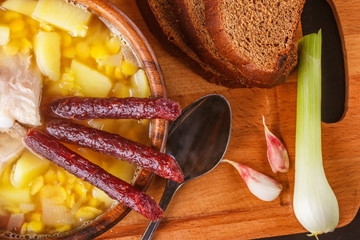 Pea soup with potatoes, pork ribs and pickled sausages in a wooden plate. Close-up