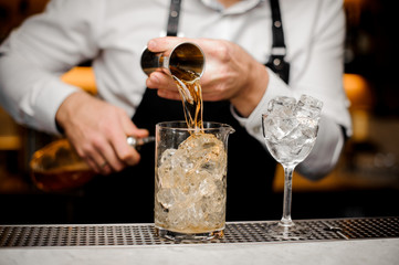 Barman pouring alcoholic drink into a large glass filled with ice cubes