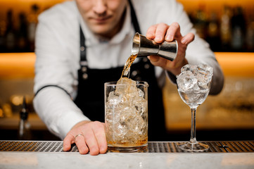 Barman dressed in a white shirt pouring alcoholic drink into a glass with ice cubes