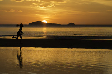 the silhouette photo of asian girl enjoy running on the beach with colorful sea in sunrise