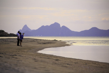 Travel and tourism. Senior family couple standing together and take photo on the beach.