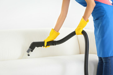 Woman removing dirt from sofa using vacuum cleaner