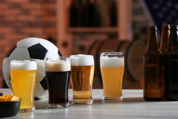 Glasses with different sorts of beer on table in football bar