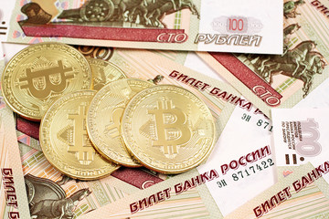 A close up image of bitcoins with Russian ruble bank notes