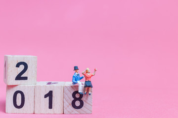 Couple sitting on wooden block number 2018