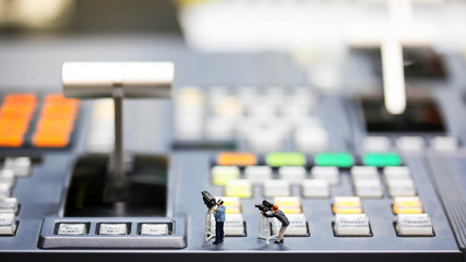 Miniature people : journalists , cameraman ,Videographer at work shooting on switcher control of Television Broadcast,color buttons