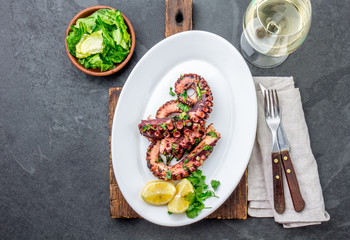 Grilled octopus on white plate serverd with white wine , top view. Seafood