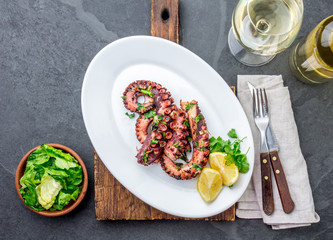 Wall Murals Ready meals Grilled octopus on white plate serverd with white wine , top view. Seafood