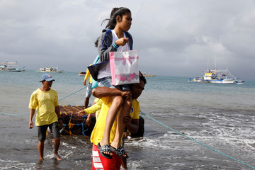 A stranded passenger is carried towards the shore after all ferry services are cancelled, a day after a Philippine vessel capsized because of bad weather in Infanta