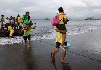 Stranded passengers are carried towards the shore after all ferry service were cancelled in Infanta, Quezon