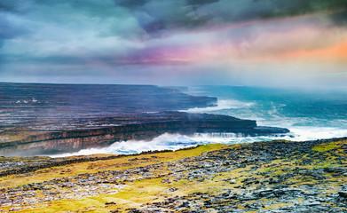 Foto op Plexiglas Blauwe jeans Irish landscape with stones, grass, rocky seashore and cloudy sky