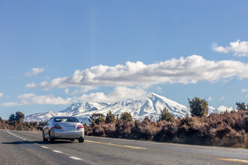 Car on the road next to Ruapehu Mount in New Zealand.