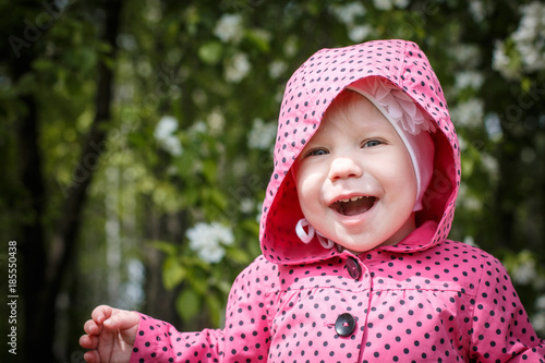 ee5cd9bea99 Portrait of a small girl in red dress in the park full of apple blossom  trees